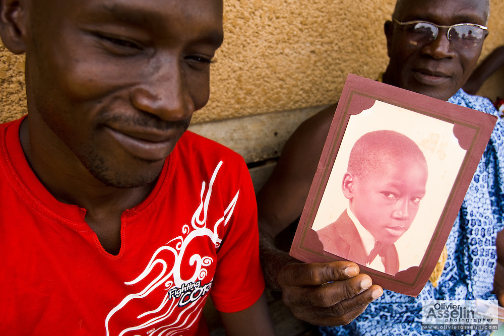 Hyacinthe Kouassi Koffi shows an old photo of his son Kevin Kouassi Gallet (left) outside their home in Tano Akakro, Cote d'Ivoire on Saturday June 20, 2009.