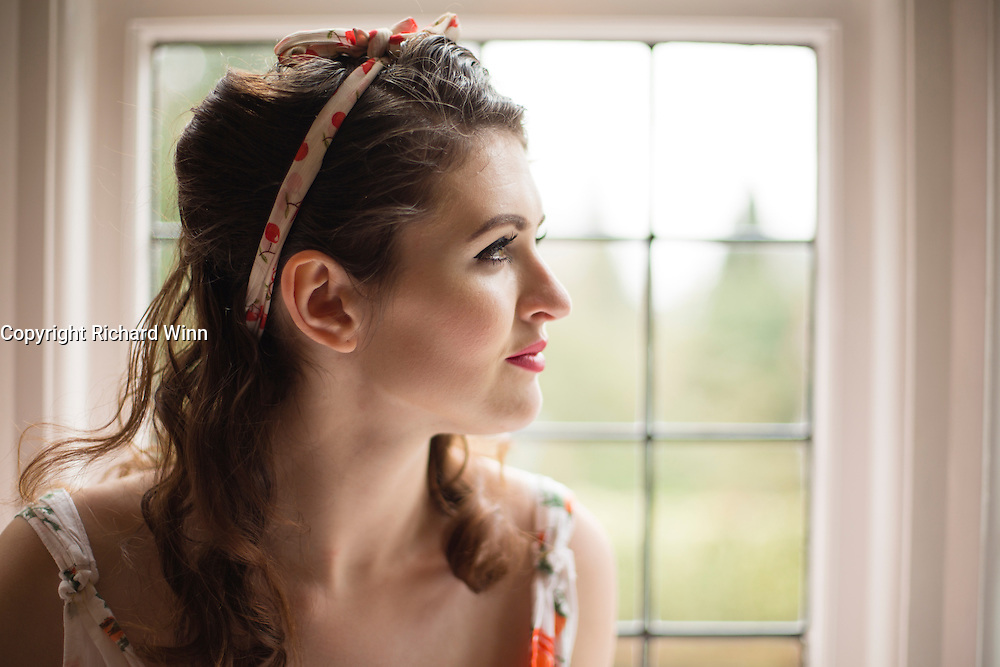 Young woman on a window sill in and old house, lit by natural light, while in a Fifties style summer dress.