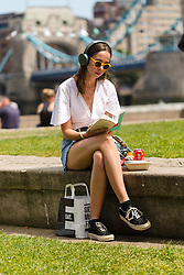 © Licensed to London News Pictures. 05/07/2019. London, UK.  A woman reads a book during warm and sunny weather near Tower Bridge in London on Friday lunchtime. The UK continues to enjoy seasonally warm weather this week, but rain is forecast across the country during the next few days. Photo credit: Vickie Flores/LNP