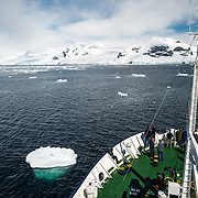 A cruise ship navigates through a channel past scattered small icebergs.