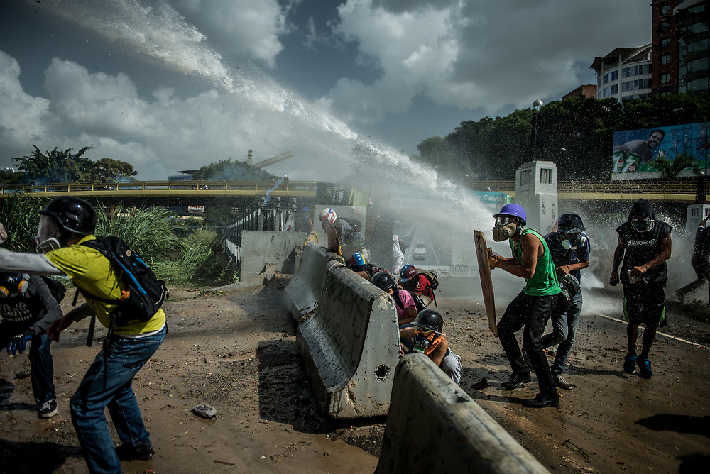 CARACAS, VENEZUELA - MAY 26, 2017:  Anti-government protesters take cover as National Guard soldiers fire a water cannon at them. The streets of Caracas and other cities across Venezuela have been filled with tens of thousands of demonstrators for nearly 100 days of massive protests, held since April 1st. Protesters are enraged at the government for becoming an increasingly repressive, authoritarian regime that has delayed elections, used armed government loyalist to threaten dissidents, called for the Constitution to be re-written to favor them, jailed and tortured protesters and members of the political opposition, and whose corruption and failed economic policy has caused the current economic crisis that has led to widespread food and medicine shortages across the country.  Independent local media report nearly 100 people have been killed during protests and protest-related riots and looting.  The government currently only officially reports 75 deaths.  Over 2,000 people have been injured, and over 3,000 protesters have been detained by authorities.  PHOTO: Meridith Kohut