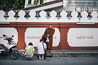 Chiang Mai, Thailand -- May 21, 2017:  A thai couple gives alms to a monk on the streets of Chiang Mai in northern Thailand.