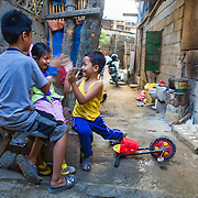 CAPTION: Brence plays with his cousins in the street outside his home. The houses here run adjacent to Marikina River, making them extremely vulnerable to flooding. There is currently an early warning system and an evacuation plan in place to save lives, but there is little they can do to protect their actual houses from flooding. LOCATION: Ampalaya Street, Barangay Tumana, Marikina City, Philippines. INDIVIDUAL(S) PHOTOGRAPHED: From left to right: Brence Ochoa, Jackelyn Sunbo and Carl Ochoa.