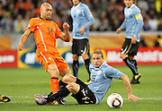 CAPE TOWN, SOUTH AFRICA- Tuesday 6 July 2010, Demy De Zeeuw kicks the ball away from Diego Perez during the semi final match between Uruguay and the Netherlands (Holland) held at the Cape Town Stadium in Green Point during the 2010 FIFA World Cup..Photo by Roger Sedres/Image SA