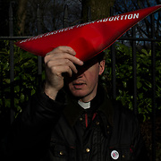 A catholic priest attempts to cover his face during an anti-abortion rally throughout Dublin City centre, on March 10, 2018.