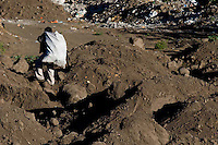 A man searches through a garbage dump near the makeshift town in Tzanchaj , Guatemala on Wednesday, March 21, 2007. A deadly mudslide here was spawned by rains associated with Hurricane Stan in October 2005. Initially, up to 500 Tzujutil Maya villagers were believed to have been killed in Panabaj by the mudslide, which essentially  wiped away the town. Construction in the shelter town was halted after the area was deemed to be of high risk. Forensic anthropologists from the Fundación de Antropología Forense de Guatemala have been working to unearth the bodies of the missing and have recovered more than 100. They have also found the number of missing to be lower than originally thought, after many people were located in shelters or living in other towns after the disaster.