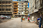 "12 DECEMBER 2012 - BANGKOK, THAILAND:  A family of demolition workers walk through the buildings they are tearing down ""Washington Square"" a notorious entertainment district off Sukhumvit Soi 22 in Bangkok. Demolition workers on many projects in Thailand live on their job site tearing down the building and recycling what can recycled as they do so until the site is no longer inhabitable. They sleep on the floors in the buildings or sometimes in tents, cooking on gas or charcoal stoves working from morning till dark. Sometimes families live and work together, other times just men. Washington Square was one of Bangkok's oldest red light districts. It was closed early 2012 and is being torn down to make way for redevelopment.    PHOTO BY JACK KURTZ"