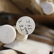 Turned baseball bats are stored in sizes, awaiting spray painting at the Tucci Lumber Company, which makes baseball bats. Norwalk, Connecticut, USA. 27th June 2014. Photo Tim Clayton