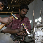 Pandian Adhaven, center, a fisherman, helps other local fishermen fix the engine of his fishing boat in a workshop set up by villagers and a volunteer from AID India in Perumalpettai, a fishing village in Tamil Nadu, India, on January 15, 2005. The area was struck by the Indian Ocean Tsunami on December 26, 2004, killing 37 of the villagers and destroying nearly all of their fishing boats. Generated by an earthquake on the ocean floor, the tsunami devastated the fishing industry along the southeastern coast of India.