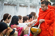 "11 MARCH 2013 - LUANG PRABANG, LAOS:  Women give food to Buddhist monks during the tak bat in Luang Prabang. The ""Tak Bat"" is a daily ritual in most of Laos (and other Theravada Buddhist countries like Thailand and Cambodia). Monks leave their temples at dawn and walk silently through the streets and people put rice and other foodstuffs into their alms bowls. Luang Prabang, in northern Laos, is particularly well known for the morning ""tak bat"" because of the large number temples and monks in the city. Most mornings hundreds of monks go out to collect alms from people.   PHOTO BY JACK KURTZ"