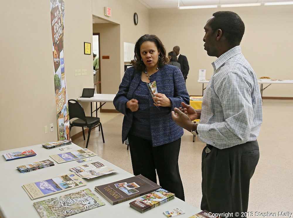 Lanisha Cassell (from left) talks with Primus Mutasingwa, of Cutting Edge Safaris, both of Cedar Rapids, during a meeting of RED-I at the African American Museum of Iowa in Cedar Rapids on Thursday, December 12, 2013.