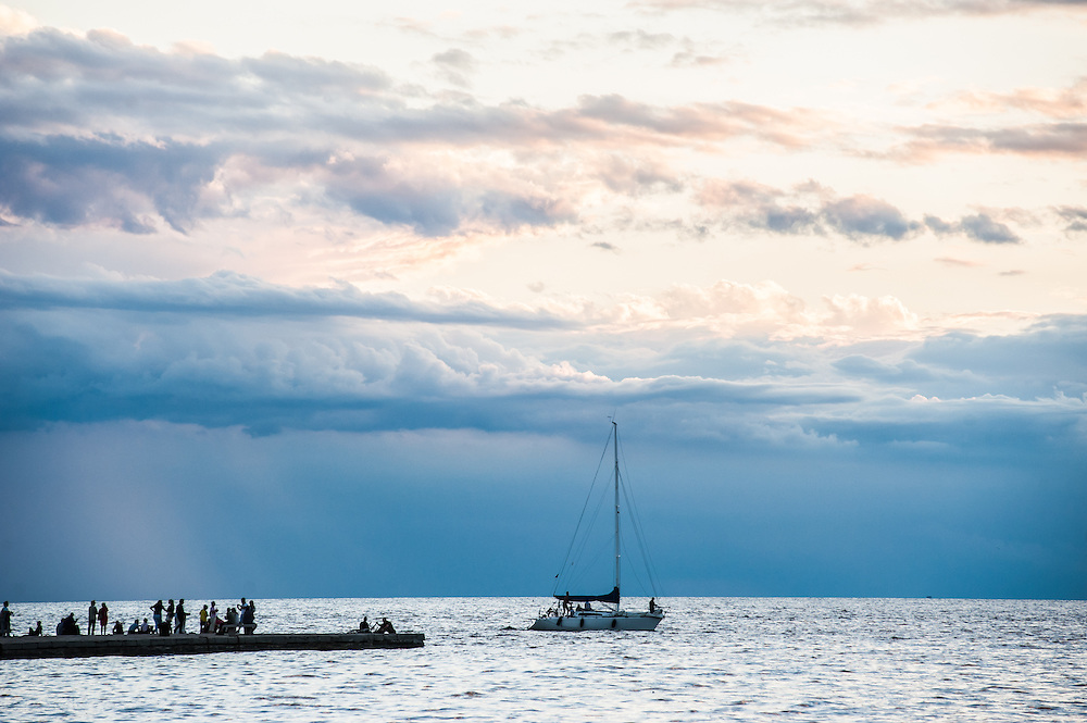 A sailing boat passes in front of the Molo Audace in Trieste, Italy