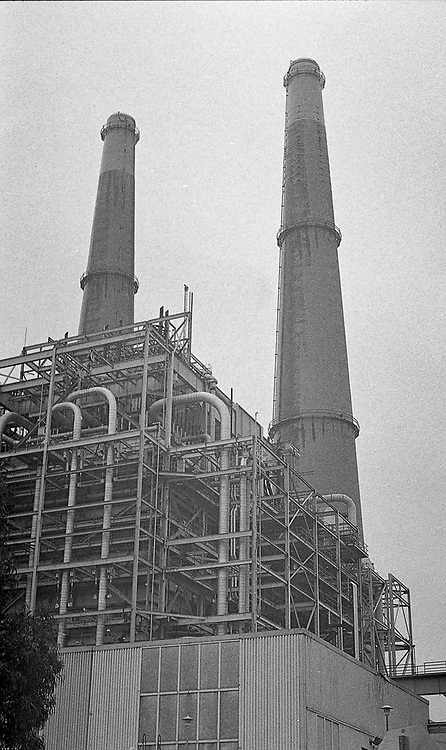 Black and white film photograph of smoke stacks at an energy plant in California.
