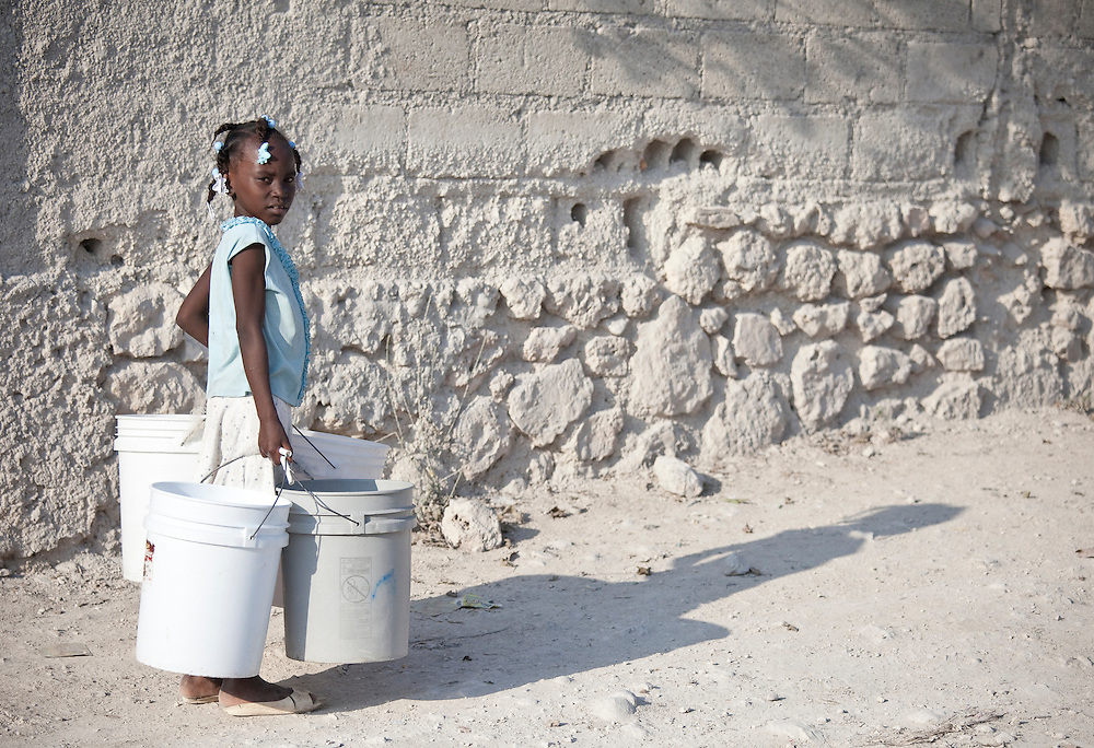 A girl carries four buckets of water down the street in Anse a Galet, Ile de la Gonave, Haiti