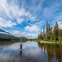 fisherman in two medicine lake casting a fly in glacier national park,