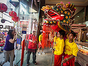 """19 FEBRUARY 2015 - BANGKOK, THAILAND: Chinese dragon dancers perform for Chinese New Year in a jewelry business on Yaowarat Road in Bangkok. 2015 is the Year of Goat in the Chinese zodiac. The Goat is the eighth sign in Chinese astrology and """"8"""" is considered to be a lucky number. It symbolizes wisdom, fortune and prosperity. Ethnic Chinese make up nearly 15% of the Thai population. Chinese New Year (also called Tet or Lunar New Year) is widely celebrated in Thailand, especially in urban areas that have large Chinese populations.    PHOTO BY JACK KURTZ"""