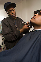 Young man shaving a customers facial hair