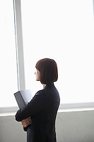 Business woman stands with file looking out of window