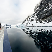 "An Antarctic cruise ship passes through glassy waters of the Lemaire Channel, as the mountains along the shore are reflected on the water. The Lemaire Channel is sometimes referred to as ""Kodak Gap"" in a nod to its famously scenic views."
