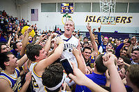 Grand Island Senior High's Casey Burnham is hoisted up by his classmates after the Islanders' 41-34 overtime win over Kearney Saturday night in Grand Island. (Independent/Matt Dixon)