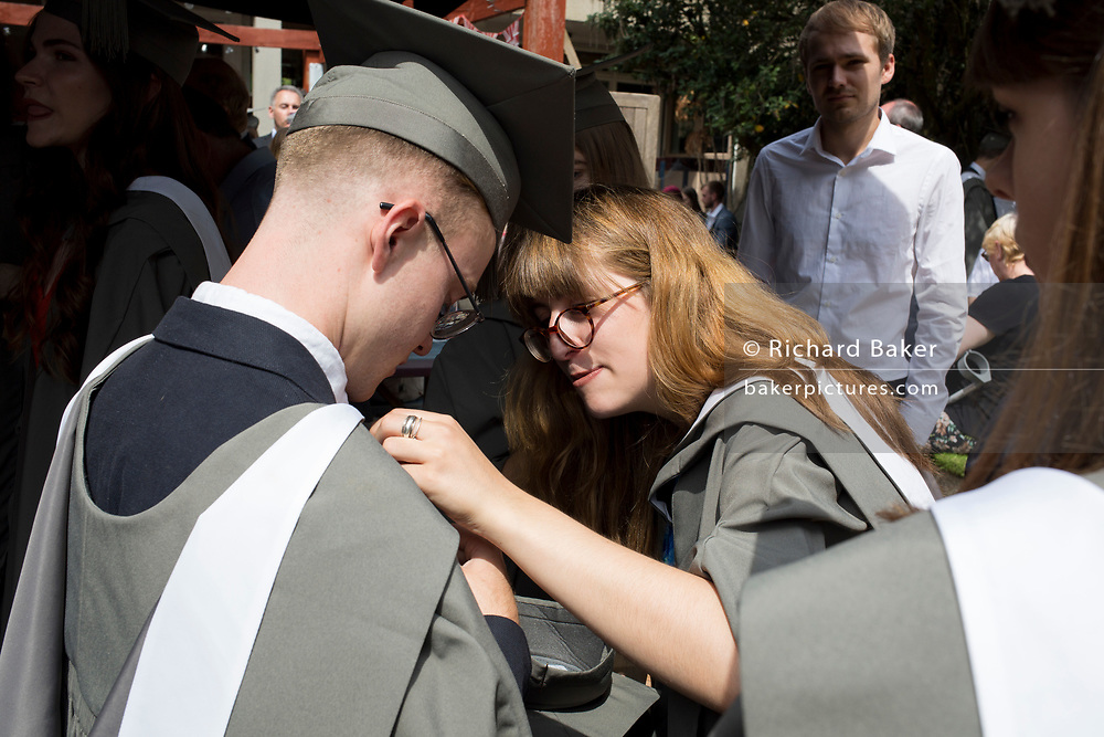 A young woman graduand adjusts a friend's rented gown at a private drinks party before their university graduation ceremony, on 13th July 2017, at the University of York, England.