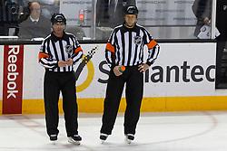Jan 19, 2012; San Jose, CA, USA; NHL referee Greg Kimmerly (left) and referee Steve Kozari (right) during a stoppage in play between the San Jose Sharks and the Ottawa Senators during the first period at HP Pavilion. Ottawa defeated San Jose 4-1. Mandatory Credit: Jason O. Watson-US PRESSWIRE