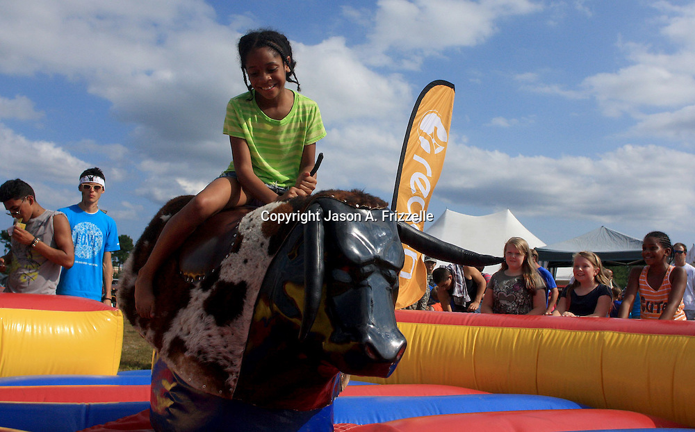 Jayda Rascoe, 9 rides a mechanical bull during the Town of Leland's Founder's Day Saturday September 14, 2013. (Jason A. Frizzelle)