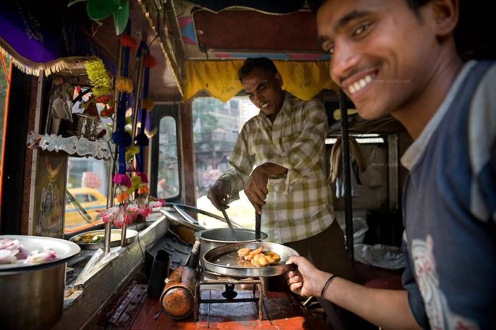 Truck drivers cook their lunch in the cabin of the truck at Kolkata's fruit market