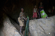 Jin returns to the cave after having collected water in bamboo tubes from the nearby river.<br /> <br /> Evidence suggests that the Maniq, a Negrito tribe of hunters and gatherers, have inhabited the Malay Peninsula for around 25,000 years. Today a population of approximately 350 maniq remain, marooned on a forest covered mountain range in Southern Thailand. Whilst some have left their traditional life forming small villages, the majority still live the way they have for millennia, moving around the forest following food sources. <br /> <br /> Quiet and reclusive they are little known even in Thailand itself but due to rapid deforestation they are finding it harder to survive on the forest alone and are slowly being forced to move to its peripheries closer to Thai communities.