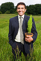 Portrait of a late 30's early 40's mixed ethnicity (spanish french hispanic italian) businessman standing in a field of high grassholding a small potted plant...Model Release: 20080602_MR_A