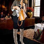 NLD/Amsterdam/20100328 - Veiling voor Engelen van Oranje, Fanny Koopmans, partner van Boy Waterman toont Cartier Marcello tas ingebracht door Bouchra van Persie