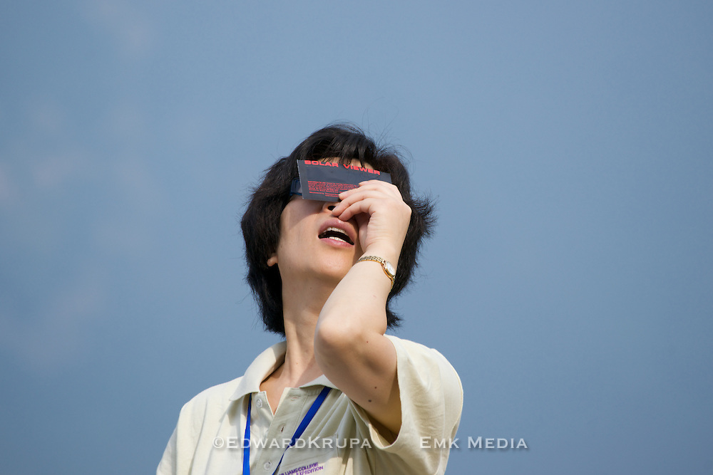 Woman looking through a solar viewer as she waits for the total solar eclipse in Tianhuangping China 2009.