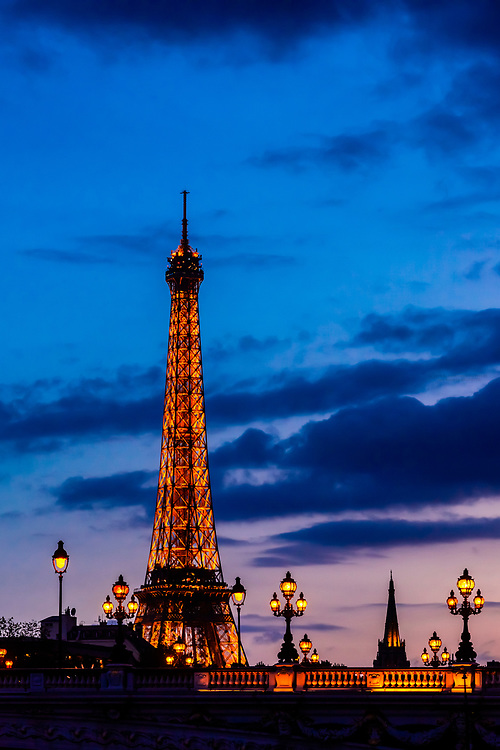 Illuminated art nouveau lamps of the ornate Pont Alexandre III (bridge) with the Eiffel Tower in background, Paris, France.