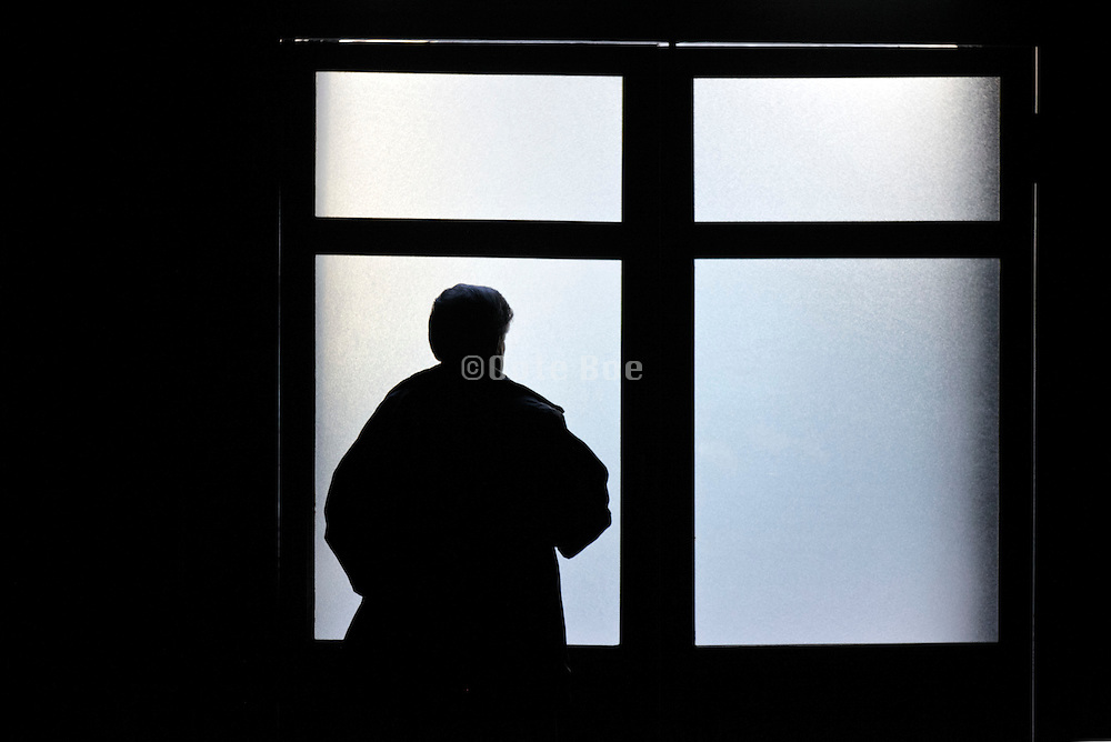 silhouetted man in front of a double door with frosted glass