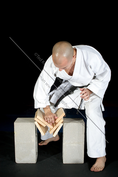 A black belt karate expert brakes a wooden board with his bare hand.  The image was photographed using high speed flash to freeze the motion taking place in 1/15,000th of a second. ..