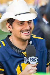 "Sep 26, 2015; Morgantown, WV, USA; Country music singer Brad Paisley conducts an interview after performing ""Country Roads"" prior to kickoff at Milan Puskar Stadium. Mandatory Credit: Ben Queen-USA TODAY Sports"