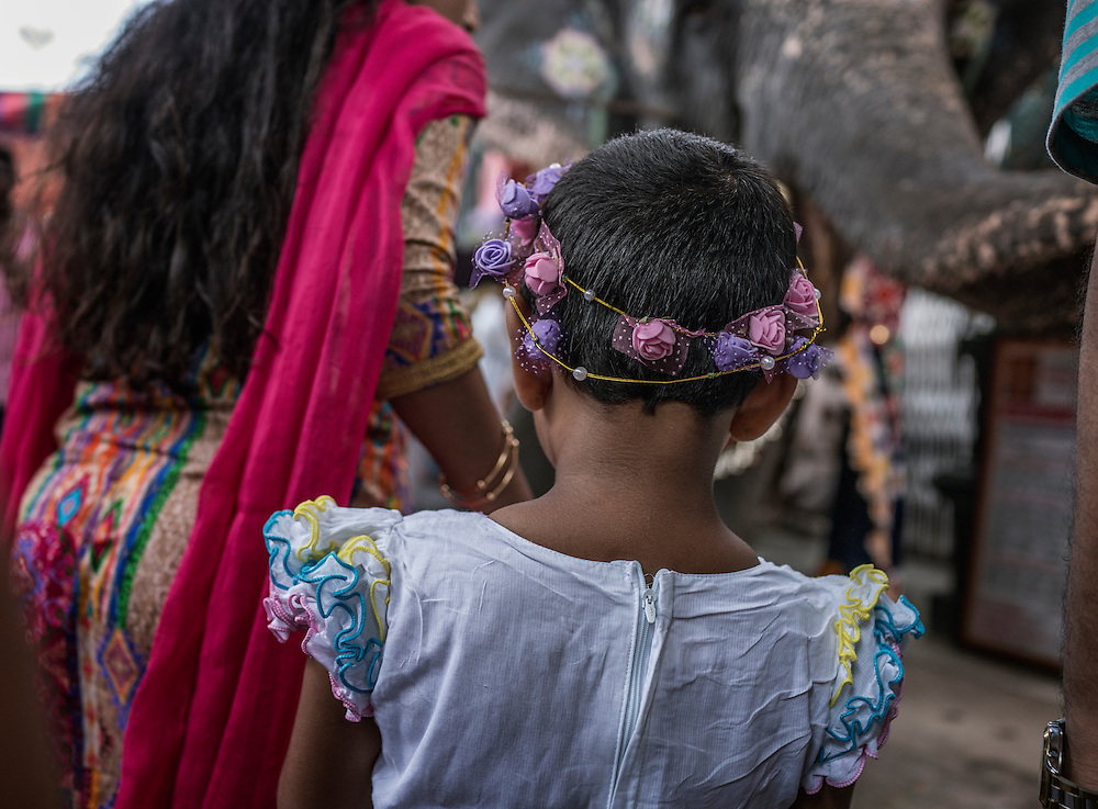 Young girl waits with her mother to be blessed with the trunk of a temple elephant, a stand in for Ganesha, at the Ganesh Chaturthi Festival at Arulmiga Manakula Vinayagar Temple.  Pondicherry, India.