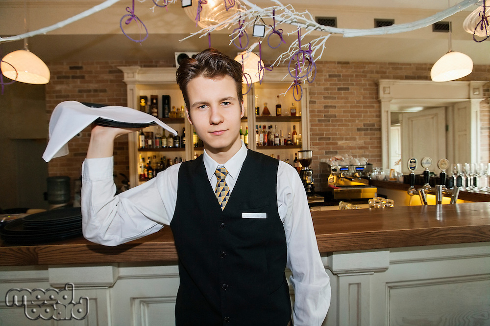 Portrait of confident waiter carrying serving tray in restaurant