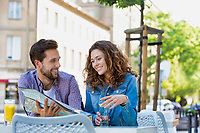 Young attractive couple smiling while looking at the menu in restaurant