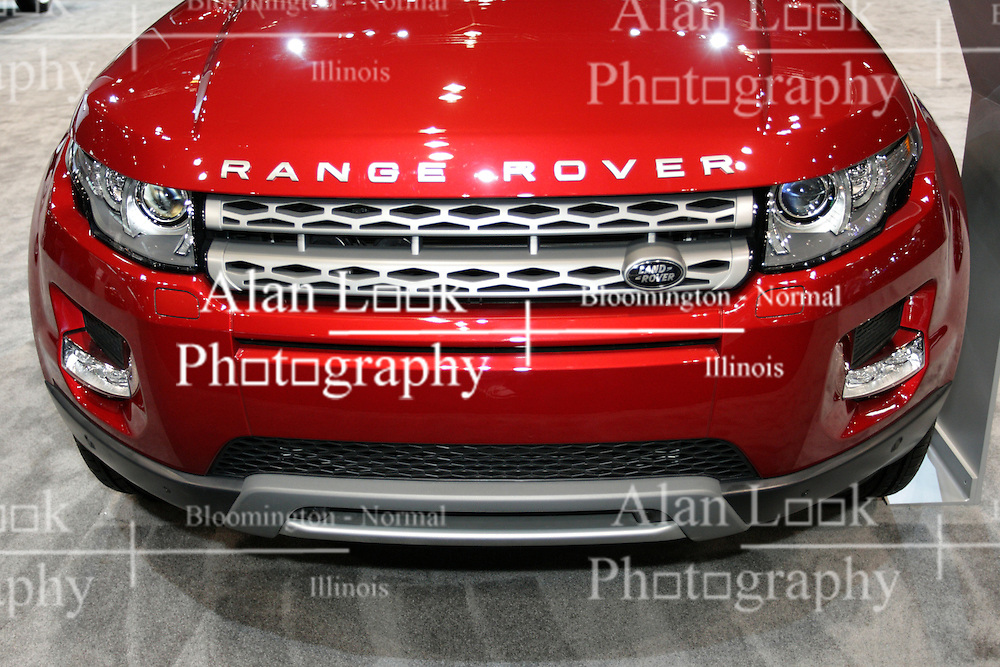 """08  February 2013: 2013 Range Rover Evoque 5 door Sport Utility Vehicle (SUV). Chicago Auto Show, Chicago Automobile Trade Association (CATA), McCormick Place, Chicago Illinois<br /> <br /> 2013 LAND ROVER RANGE ROVER EVOQUE: Introduced for 2012, the Range Rover Evoque targets a new generation of Range Rover enthusiasts, starting with a bold, dynamic profile and distinctive taper to the """"floating"""" roofline. It maybe the smallest, lightest and most fuel-efficient Range Rover ever produced, but the 2013 Range Rover Evoque stays true to the core brand values by providing premium levels of craftsmanship, luxury, performance and multi-terrain capability. Offered in a choice of coupe and five-door body styles, the Evoque is available in three trim levels, each with its own distinctive character. For cool and contemporary, there is the Evoque """"Pure,"""" with aluminum alloy roof. Then there is the luxurious """"Prestige"""" and the bold and sporting """"Dynamic,"""" with standard panoramic laminated glass roof. All models provide five passenger seating, while the coupe exclusively offers a package that uses individual rear seats, for a 2+2 cabin. When it comes to hauling groceries or sports gear, the Range Rover Evoque offers a wide, deep cargo area. With the rear seats folded, the five-door provides 51 cu.-ft. of space, the coupe slightly less at 47.6 cu.-ft. All Range Rover Evoque models are powered by a 2-liter, 240 horsepower direct-injected turbocharged four-cylinder engine, which is teamed to a six-speed automatic transmission and a full-time, intelligent four-wheel drive system. New this year is a revised front grille design that includes the black Land Rover logo, new contrast roof color as a stand-alone option, and to aid in exploring unmapped areas, Land Rover Off-Road navigation has been added to the Range Rover Evoque for 2013."""