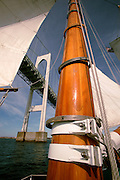 Adironack Schooner with wooden mast sailing under Newport Bridge, Newport, RI