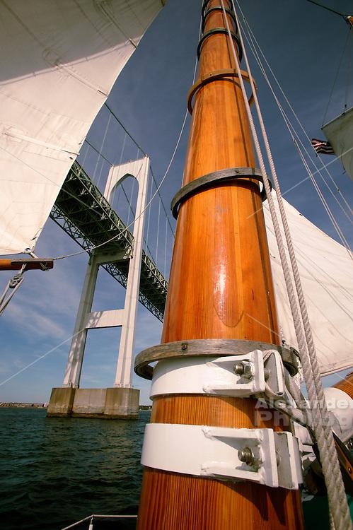 Adironack Schooner with wooden mast sailing under Newport Bridge, Newport, RI