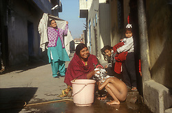 Child being washed in the street by mother; hair covered in soap; in Punjab; India,