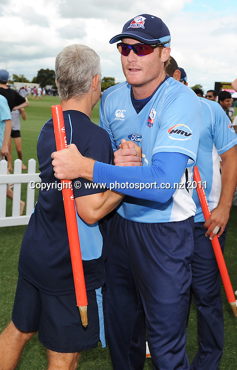 Martin Guptill with a souvenir wicket hugs coach Paul Strang after winning the HRV Twenty20 Cricket Final between the Auckland Aces and Canterbury Wizards at Colin Maiden Oval in Auckland, New Zealand on Sunday 22 January 2012. Photo: Andrew Cornaga/Photosport.co.nz