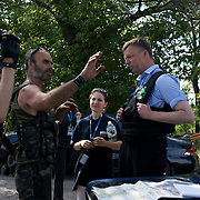 OSCE spokesperson Alexander Hug and a local rebel leader, negotiate safe passage for the International expert team members looking for evidences at the crash site of the Malaysia Airlines flight MH17 in Grabovo, a small rural village in the province of Donetsk, eastern Ukraine. Malaysia Airlines flight MH17 was travelling from Amsterdam to Kuala Lumpur when it crashed killing all 298 on board including 80 children. The aircraft was allegedly shot down by a missile and investigations continue over the perpetrators of the attack.
