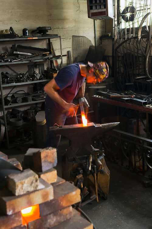 Blacksmith working on red hot steel with hammer and anvil in his workshop