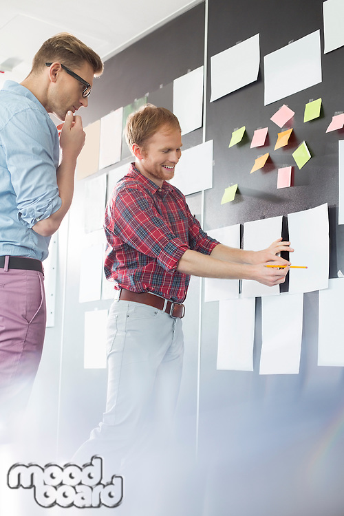 Creative businessmen discussing over document on wall in office