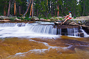 Woman relaxing by cascade on the Tuolumne River,  Yosemite National Park, California