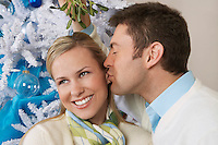 Man kissing woman under mistletoe