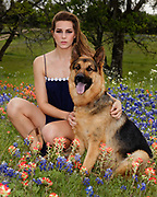 Portrait of fashion model Tayler Campbell in field of bluebonnets with her German shepherd dog.